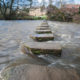 Stepping stones across a small river in english rural village countryside scene.