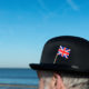 Englishman with bowler hat with union jack flag pinned on the hat  on the beach overlooking the sea and towards Europe.