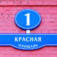 """Street signs with an inscription in Russian """"Red Square the building number one"""" in Moscow Russia on a wall from a red brick"""