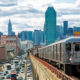 Train approaching  elevated subway station in Queens, New York. Finanancial buildings and New York skyline are seen in the background, on the left below can be seen a busy street full of cars at rush hour, cloudy, dramatic sky, horizontal orientation, USA