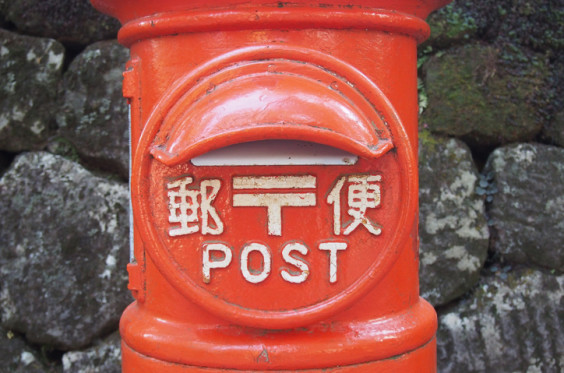 red postbox with stone background in Japan