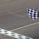 A checkered flag waving at an car race. Waving check flag in air at race finish, motion blur on flag.