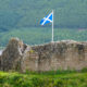 Scottish flag placed on an old stone wall near a lake