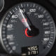 Close-up showing a rising speedometer needle moving past 70mph towards 80mph on a modern high-performance sports car.